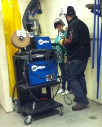 Jacob Gitter teaches a student how to weld.
